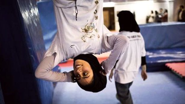 Mahsa-Khakbazan-an-Iranian-woman-who-practices-parkour-hangs-from-a-bar-during-a-training-session-at-a-sports-hall-in-northern-Tehran-on-March-12-2014-AFP