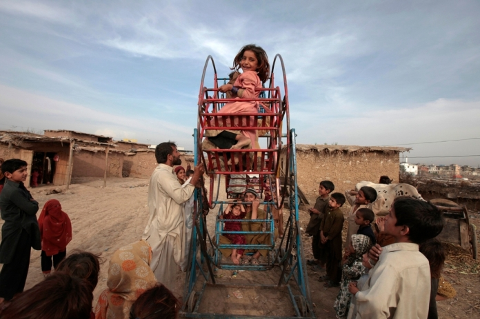 An Afghan girl smiles as she rides on a hand-operated ferris wheel with other children in a slum on the outskirts of Islamabad March 19, 2013. REUTERS/Faisal Mahmood (PAKISTAN - Tags: SOCIETY)