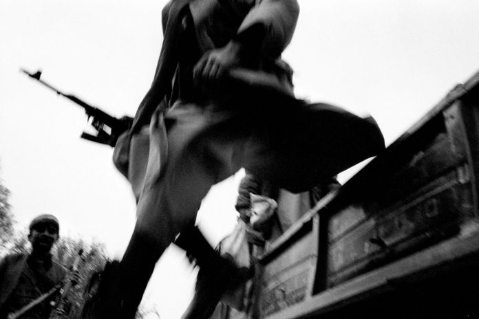 AFGHANISTAN. Kalakata front line, Northeast region. A Northern Alliance soldier jumps out from the truck bringing him to the front line. 2001.