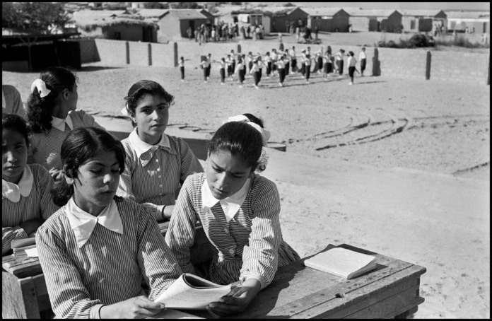 DEIR EL BALAH (The Monastery at the Sea) Camp in Jabalya near Gaza.This is one of the best camp schools for refugee girls.They wear self made uniforms, desks have been made by refugee boys in the carpentry shop. In the background girls are having a sports class, behind the schoolyard, are the mud huts of the camp.