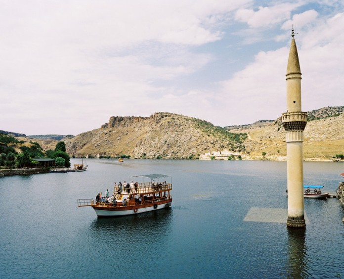 A tourist boat tour is visiting the former Savaçan Village flooded by the reservoir lake of the Birecik Dam on the Euphrates river. Turkey