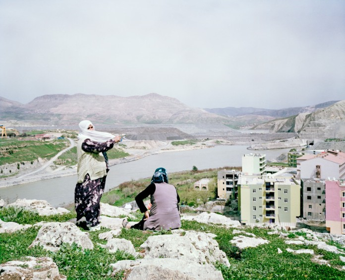 Women are standing on top of the dam construction site and city of New Ilisu where construction are being built and resort hotel for the hot springs. Turkey